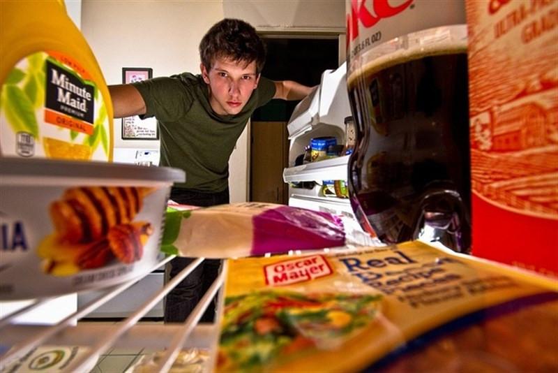 Chico mirando la comida que hay en la nevera