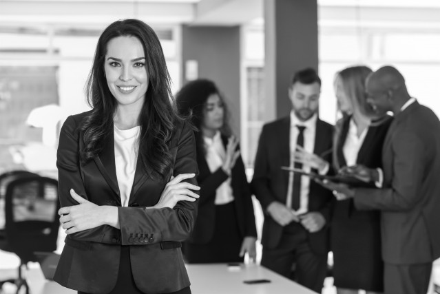 Archivo - Líder empresaria mirando a cámara en la oficina moderna con empresarios multiétnicos que trabajan en segundo plano